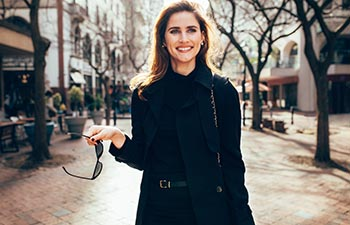 Beautiful caucasian woman walking along the road in the city.