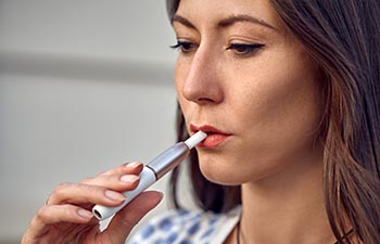 Close-up of a girl smoking an electric hybrid cigarette.