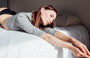 Brunette woman in underwear lies on the bed.