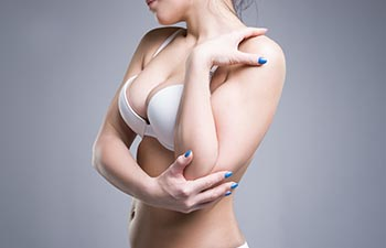 Woman in white push up bra on gray background.