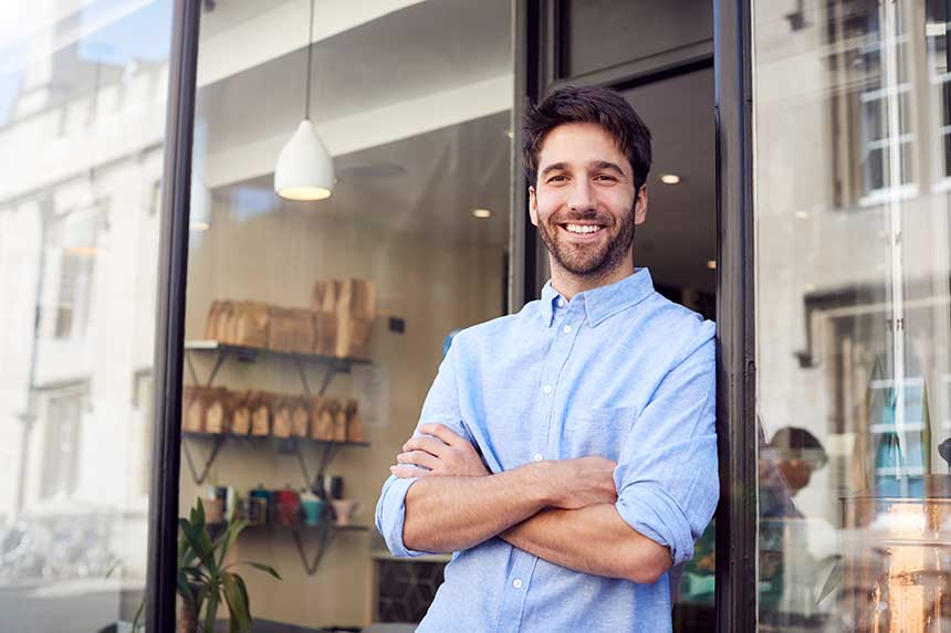 Cheerful handsome man standing outside coffee shop