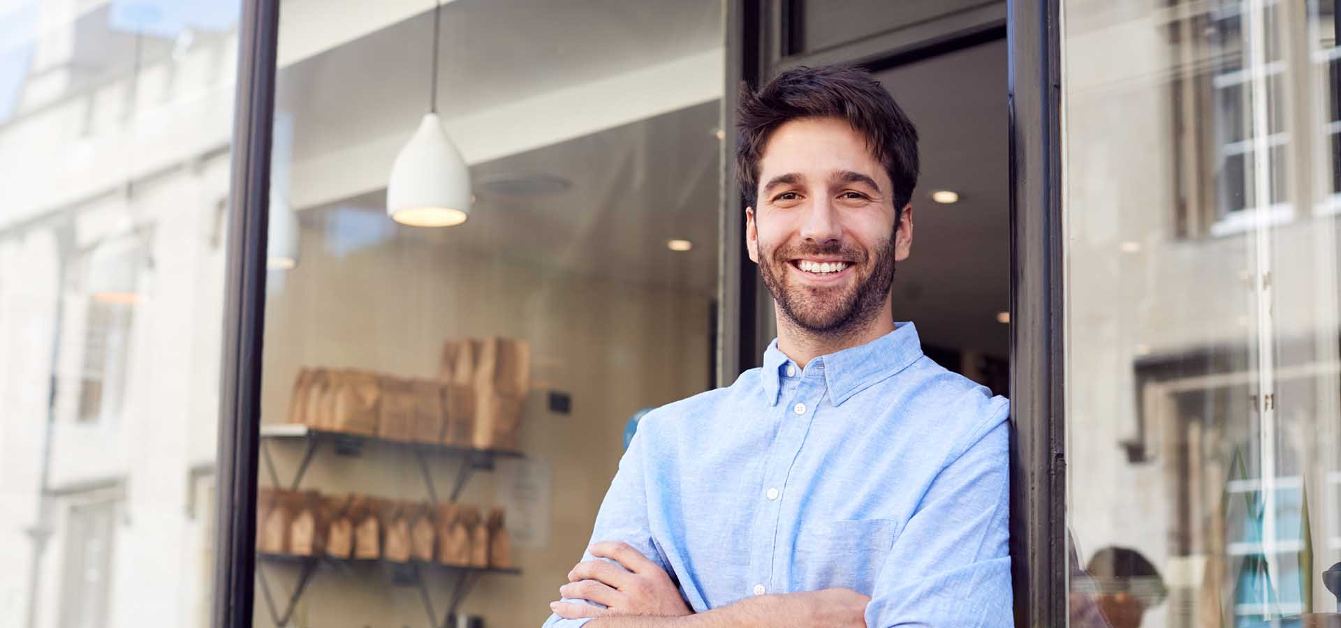 Portrait of male owner standing outside coffee shop