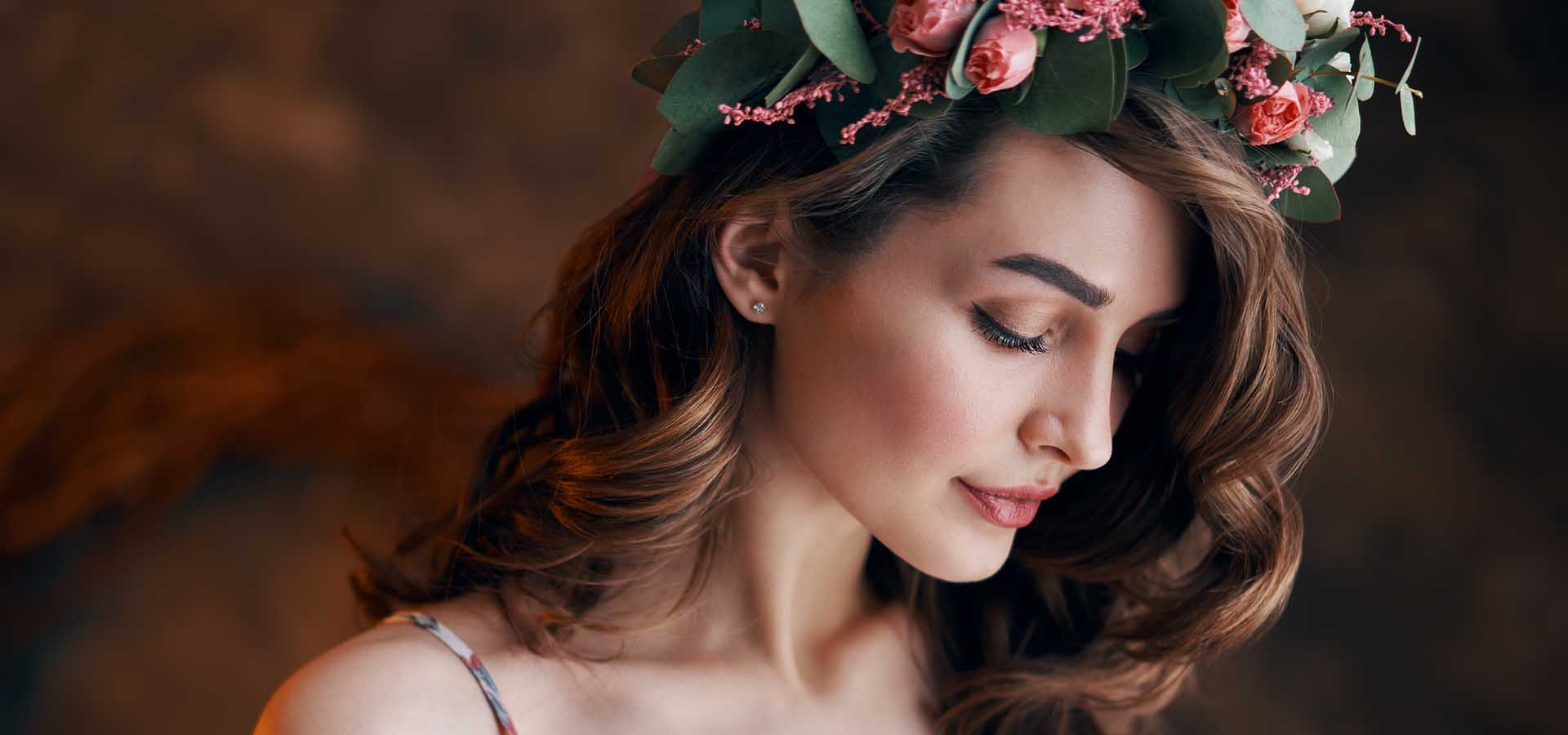 Beauty portrait of young woman with wreath of flowers in her hair.