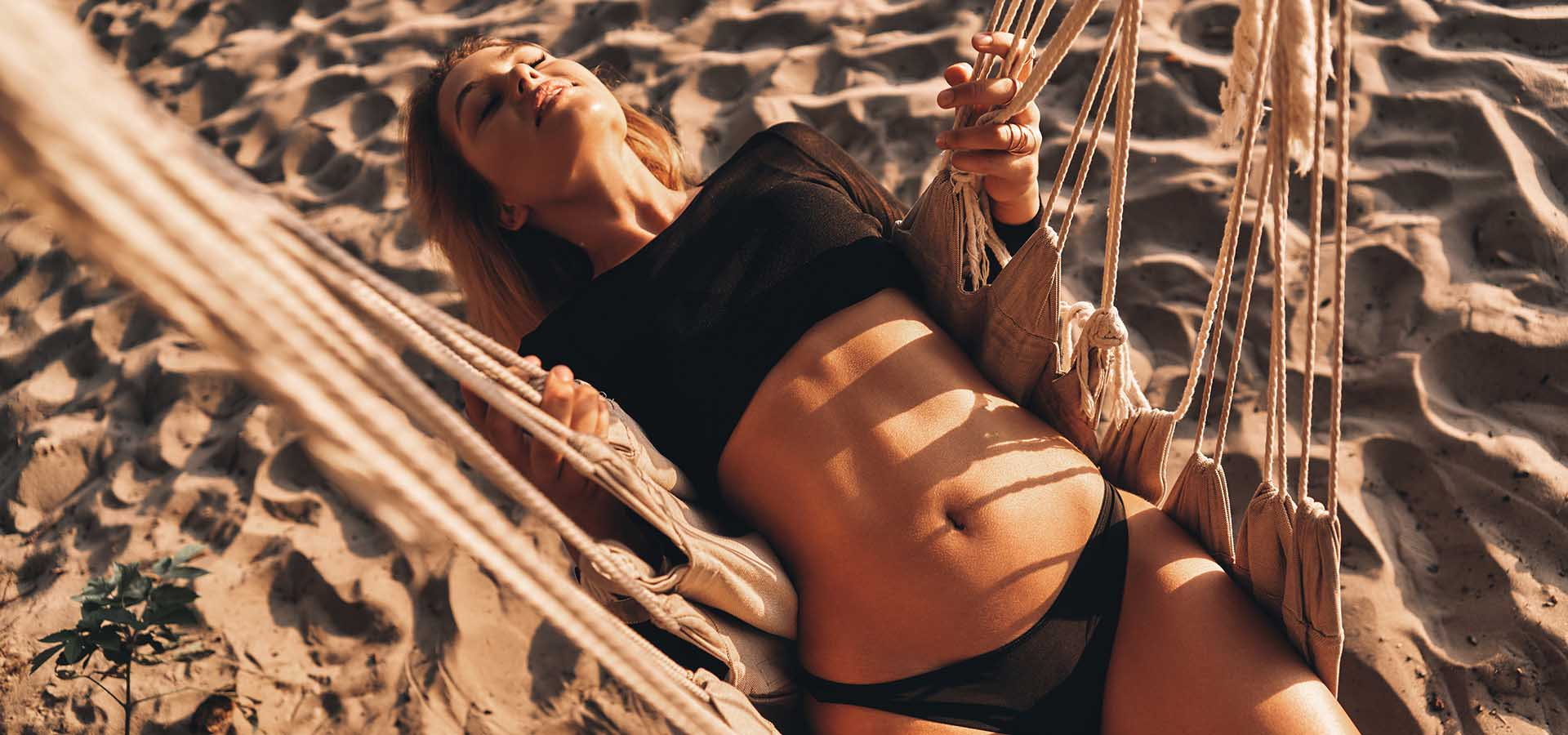 Top view of attractive young woman smiling while lying down in hammock on the beach.