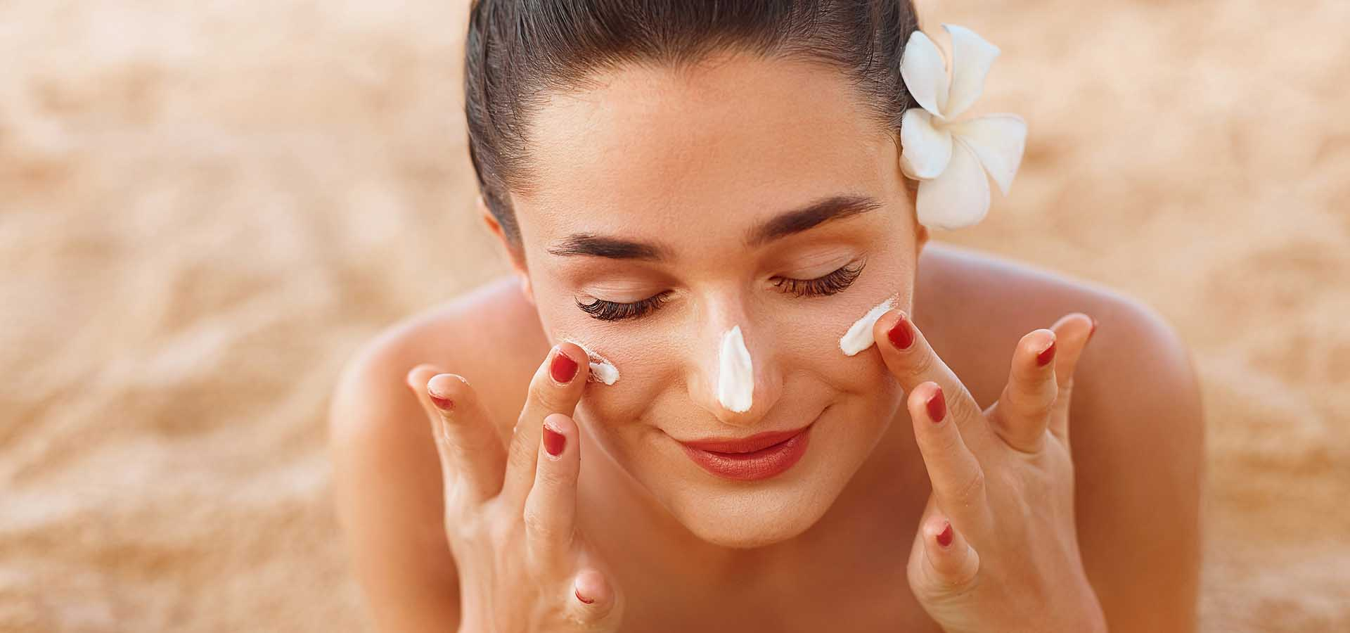 Beautiful happy cute woman applying suntan cream to her nose on the beach